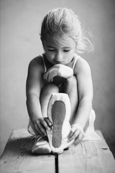 This isn't just a picture of a little girl putting her dance shoes on, it shows her smirking to herself getting ready to unleash her weapons of dancing skills!