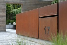 Contemporary corten fence, contrasts with weathered wood, gravel, grasses, design by Filip Van Damme