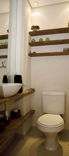 """O lavabo criado pela arquiteta Adriana Fontana possui apenas 1,50m, mas esbanja soluções decorativas. A primeira delas foi alongar a prateleira que sustenta a cuba ao máximo, garantindo uma aparência de horizontalidade. """"É como uma ilusão de ótica. A prateleira, de madeira de demolição, deu a sensação de que o banheiro é um pouco maior do que a realidade"""", explica Adriana. O espaço da parede que fica acima do vaso também foi aproveitado com prateleiras, que acomodam objetos decorativos."""