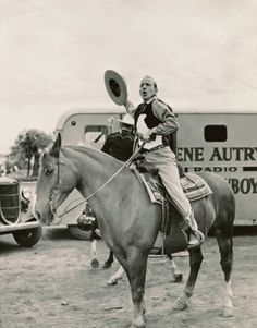 """At last, here I am at the peak of me power, ha-cha-cha!!"" Jimmy ""Schnozzle"" Durante cheers as he successfully reaches the deck of the tamest horse in the Gene Autry stable. ""What a man! What a cowboy! Where's me rope and gun!"" Durante clanked a mean spur with Autry and Ann Miller in ""MELODY RANCH"" at Republic Studio. In the background here is Autry heading into his stable trailer. (from Steve Crum's show biz memorabilia collection)"