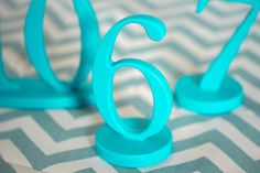 custom made teal wedding table numbers - so pretty and fun! maybe just spray paint candles and cut off the wicks and glue onto stands?
