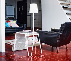 IKEA PS 2014 side table with light in the middle of a room together with an old leather sofa and IKEA PS 2014 rug