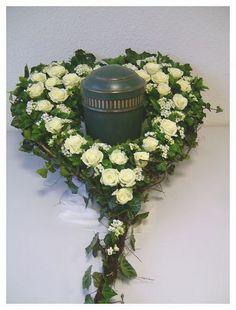 Die Urne wird bei der Beerdigung / Trauerfeier mittig im Blumen-Herz platziert. Die Herzen mit Steckmasse sind speziell für Urnen-Grabgestecke ausgelegt