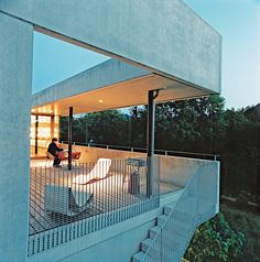 The rear deck of a concrete prefab home outside of Zurich seems to float in a leafy canopy and offers an amazing view of the nearby Rhine.