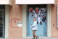 A man walks past the 'Super Pope Francis' graffiti in a street of L'Aquila five years after the earthquake on March 22, 2014 in L'Aquila, Italy. (Photo by Franco Origlia/Getty Images)