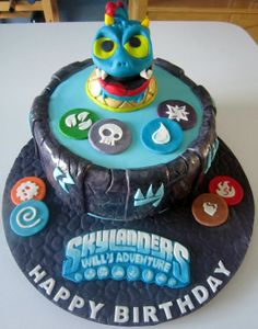 """A Skylanders cake to mark a """"triple birthday party."""" The Happy Birthday message isn't specific because it's aimed at three people. This year's cake is for my nephew, Will, thus his name on the Skylanders's logo. The tokens/chips are part of the Skylanders's game, representing eight different """"elements"""": fire, water, etc. This is Wrecking Ball (his eyes are also wonky on the figurine though I know they look weird). I learned a lot about forming figures with this cake - mostly what NOT to do!"""