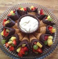 ijshoorntjes in chocolade, gevuld met fruit en extra slagroom