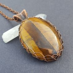 Golden tigers eye and copper necklace. Handmade with lots of love and care, this natural stone pendant is one of a kind. This tiger's eye stone has a soft glow and shines in the sunlight. It is created with oxidized copper.   New in the #Etsy store: http://etsy.me/2F50bnz