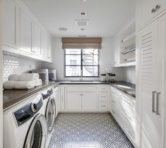 A white and gray laundry room clad in black and white mosaic floor tiles boasting a gift wrapping station fixed over white shaker cabinets donning chrome pulls and a dark gray quartz countertop. A white and gray laundry room clad in black Grey Laundry Rooms, Laundry Room Cabinets, Farmhouse Laundry Room, Laundry Room Design, Laundry Area, Kitchen Design, Ultra Modern Homes, White Shaker Cabinets, Gray Cabinets