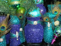 Recycle old glass or wine bottles and jars and turn them into glittery vases and decor. Pretty peacock colors!