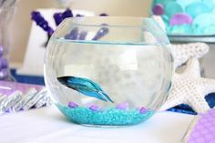 Mermaid Birthday Party idea ... Use a few fish bowls, colored rocks that match the color theme, with a Beta Fish as decoration. Then you can use them as a prize for the kids to win & take home. Serves as a double use.