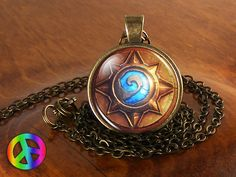 """Handmade (by me) WoW World of Warcraft Gold and Electric Blue Hearthstone Swirl Video Game Gamer Gaming Cosplay Necklace Pendant Jewelry Gift for Men / Women vintage style necklace and pendant created using solid fine antique brass, crystal clear glass, and a sturdy lobster claw clasp affixed to a long 24"""" quality brass chain that I can change length for you free of charge by request."""