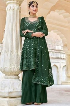 A stylish interpretation of ethnic glamour and contemporary style, this bottle green georgette sharara suit which exudes feminine charm. This sweetheart neckline and full sleeve suit adorned with resham, thread and silver zari. Teamed up with georgette sharara pants in bottle green color with bottle green georgette dupatta. Sharara pants has plain. Dupatta prettified with resham, thread and silver zari. #shararasuits #malaysia #Indianwear #weddingwear #andaazfashion Indian Attire, Indian Wear, Garara Suit, Wedding Mint Green, Pantalon Cigarette, Georgette Fabric, Costume, Sharara, I Dress