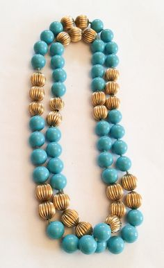 A stunning Robins Egg Blue Art Deco Necklace is featured. The beads are hand knotted, with 10 groups of sparkly gold tone accent beads. These accent