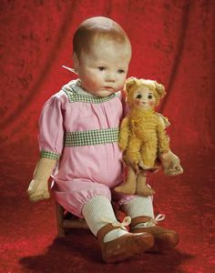 """German Cloth Character """"Du Mein"""" by Kathe Kruse,with Toy Puss in Boots Doll    20"""" (51 cm.) All-cloth doll with pressed and painted facial features,plump face,brown shaded hair with stippling details,blue shaded eyes with whtie eyedots,black and brown upper eyeliner,tinted brows,closed mouth with downcast expression,stitch-jointed arms,loosely-attached legs,wearing cotton romper suit,woolen stockings,tan leather shoes,and carrying a toy mohair Puss in Boots with glass eyes and sewn-on felt…"""