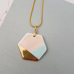 A pastel toned pink and aqua glazed porcelain pendant with 24k gold lustre detail. The porcelain pendant is attached to an 18 inch gold plated snake chain with extender. The pendant is fired 3 times to achieve this finish. The lightweight nature of this clay makes the necklace very easy
