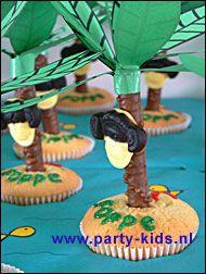 Eiland cup cake met aap in palmboom! Benodigdheden: Mix voor muffins (Dr Oetker) Schrijfstiften (Dr Oetker) Apekoppen (Katja) Lange nekken (Verkade) Stevig groen papier Plakband Poedersuiker Water muffinblikken (HEMA) Blauw papier Oranje papier