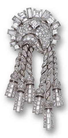 An Art Deco diamond tassel brooch, Mauboussin, Paris, circa 1935. The crescent-shaped sunburst motif supporting six articulated tassels, set with nine square-cut diamonds as well as with 51 baguette and numerous round and single-cut diamonds, mounted in platinum, signed Mauboussin, Paris, assay marks. #Mauboussin #brooch #ArtDeco