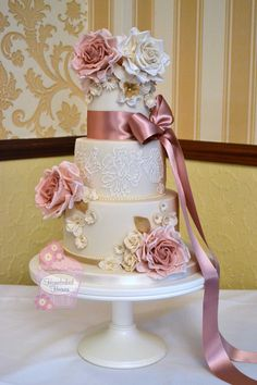 Wedding cake with dusky pink and ivory roses, daisies, fantasy flowers and royal icing lace brush embroidery inspired by the bride's wedding gown, at Kings Croft Hotel, Pontefract