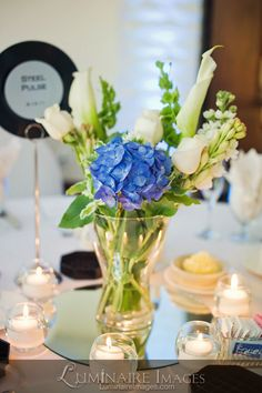 Candlelit wedding reception centerpiece with blue floral accent