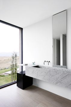 simplicity of carrara marble trough sink, black & white contemporary bathroom