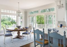 Benjamin Moore Gray Owl Kitchen and Breakfast Nook. Eat in kitchen features a Restoration Hardware Round Salvaged Wood Trestle Dining Table lined with white Vintage French Round Cane Back Fabric Side Chairs accented iwth blue seat cushions atop a blue rug illuminated by a white pagoda lantern surrounded by windows and doors. Digs Design Company.