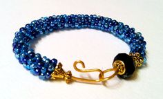 7 inch Designer bracelet with Sapphire faceted glass focal bead, handwoven lighter Sapphire Czech glass beads with antique gold-tone accented spacers, end caps & hammered clasp.  $48.00