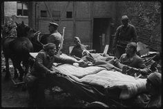 Carrying wounded soldiers from a horse carriage at an aid post.Berlin. April 1945.