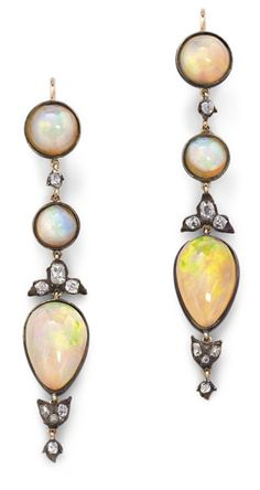 A pair of opal and diamond ear pendants, each designed as a graduating line of variously-shaped cabochon opal between old brilliant-cut diamond spacers, length 6.3 cm, total opal weight approximately 11.8 carats, ear wire fittings.