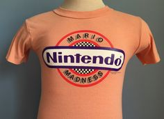Vintage 1980s tan Nintendo Mario Madness 1989 t-shirt, with multicolored image and print.  Size: Youth XL (fits like Adult Small) Brand: Top Half 50% cotton, 50% polyester  The shirt is very soft and in very good vintage condition, with no visible tears or stains.  Approximate measurements with garment laying flat (INCHES): Length (from top of shoulder at collar seam to bottom) : 23 Sleeve (from top of shoulder seam to cuff edge) : 6 Between Shoulder Seams : 14.5 Underarm to Underarm : 15.5