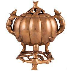 INCENSARIO EN BRONCE DORADO Compuesto por tres piezas. Ornamentación en forma de calabaza con asas en forma de animal y tapa troquelada con adornos vegetales. Medidas: 23 x 23 cm.