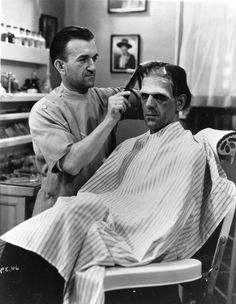 "Make-up artist Jack P. Pierce applies make-up and combs the hair of Boris Karloff on the set of ""Frankenstein"""