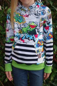 """Hier hat unsere Kundin Mandy eines unserer beliebtesten Baumwolljerseys in Szene gesetzt: Den Graffiti frog! Kaum ein anderer Stoff schafft es, das alle ins Träumen geraten, Jungs- und Mädchenmamas!Denn mit dem tollen Schnittmuster """"Leo"""" von Pattydoo mit langen Ärmeln, Kapuzenteil und Känguruhtasche sieht er richtig cool aus – für beide Geschlechter!"""