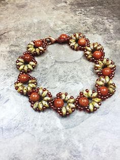 Irresistible brown flower Super duo beaded bracelet, perfect combination goldstone beads and light brown super duo beads. Measure: 7.5 inch Materials: 8mm goldstone light brown super duo