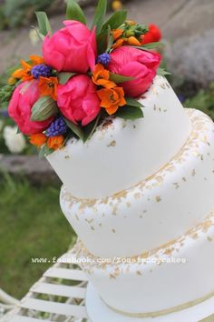 Gold and white wedding cake with real flowers.