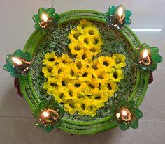 Diya arranged in flowers over leaves..