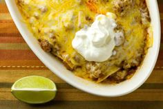 ~Enchilada Casserole~ Ingredients 1 pound ground beef 1 tablespoon taco seasoning 1 ten ounce can enchilada or taco sauce 3/4 cup water 1/2 cup salsa 12 corn tortillas 1 cup shredded Monterey Jack and/or Cheddar cheese Sour cream and lime wedges for garnish