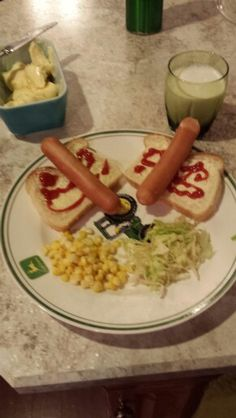 Some hot dogs with corn and salad