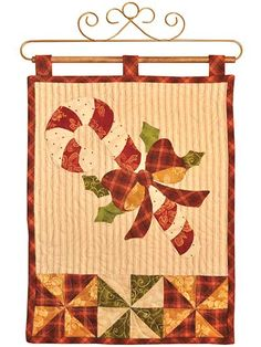 """Celebrate the Christmas season with this beautiful wall hanging!   Your home decor will be complete once you deck it out with this vintage-inspired wall hanging that features a sweet candy cane wrapped in a tidy bow. It will make a great door hanging to greet your guests, or even for giving as a housewarming present. Finished size is 12"""" x 18"""". Kit includes pattern and laser-cut fabric for top, binding, and backing."""