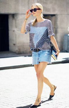Pernille Teisbaek pairs a patterned blouse with a black belt, denim skirt, and black pumps