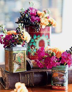 Latas de chá são ótimos vasinhos. Experimente colocá-las sobre livros antigos – o resultado é retrô e dá altura aos arranjos. Produção de Henrique Morais