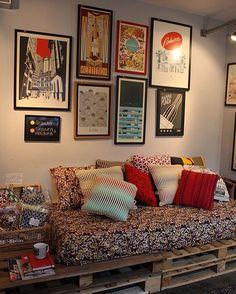 Sofá cama de pallets e ainda composição de quadros na parede.
