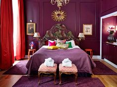 Absolutely #aubergine #bedroom color with #eclectic #design and #decor.  Love the two #stools and orange end #tables!