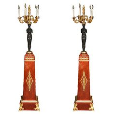 "Pair of Empire style two tones bronze and wood figural torcheres. CIRCA: 1880's/1900's DIMENSIONS: 88"" h x 18"" w x 18"" d"