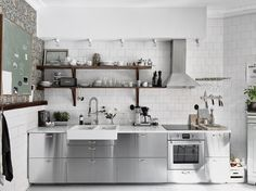 William Morris wallpaper in a modern silver and white kitchen with wood accents.