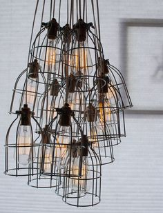 """cage light from jak home. """"12 galvanized, industrial light bulb cages artfully clustered to form a chic and sculptural pendant light fixture."""" $2950"""