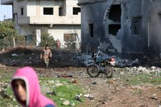 Young Syrians walk by a bombed out building.