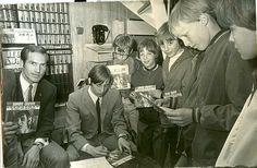 Johan zet handtekeningen op zijn eerste grammafoonplaatje, onder het toeziend oog van René Leijen (met bril)