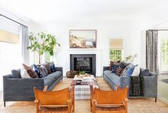 Boho inspired living room with denim sofas, leather armchairs, and a fireplace