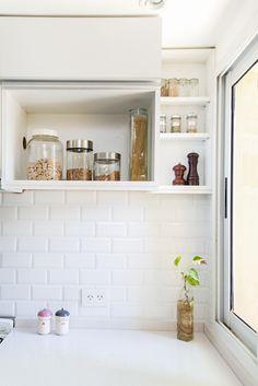 Cocina con muebles de melamina blanca con manijas de aluminio. Mesadas de Silestone. Revestimiento sobremesada tipo subway tile biselados blancos.